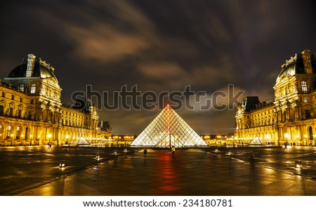 PARIS - OCTOBER 12: The Louvre Pyramid on October 12, 2014 in Paris, France. It serves as the main entrance to the Louvre Museum. Completed in 1989 it has become a landmark of Paris. - stock photo
