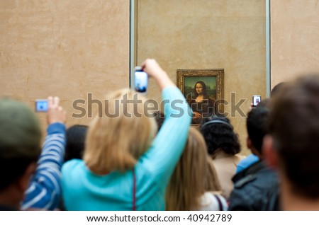 "PARIS - OCTOBER 24: Visitors take photo of Leonardo DaVinci's ""Mona Lisa"" at the Louvre Museum, October 24, 2009 in Paris, France. The painting is one of the world's most famous. - stock photo"