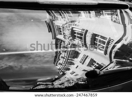 Paris reflected in the car window. Travel concept. Reflection of buildings and the sky with clouds. Aged photo. Black and white. - stock photo