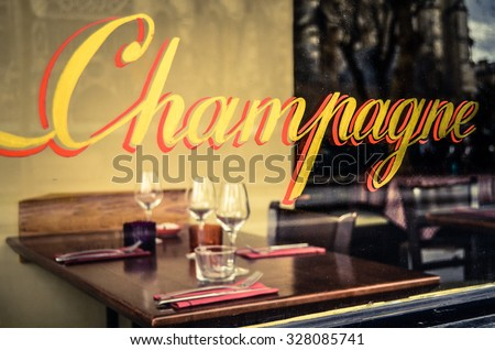 Paris Restaurant With Champagne Sign In The Window With Place Settings And Wine Glasses - stock photo