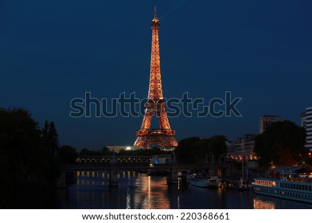 PARIS - SEP 27: The illuminated Eiffel Tower on Sep 27, 2014 in Paris, France.The Eiffel tower is most visited monument of France with 6 million visitors every year - stock photo