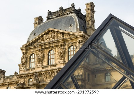 PARIS - SEPT 17, 2014: The Louvre Palace and IM Peis Pyramid. The Louvre Museum is one of the world's largest museums and a historic monument in Paris, France. A central landmark and popular place. - stock photo