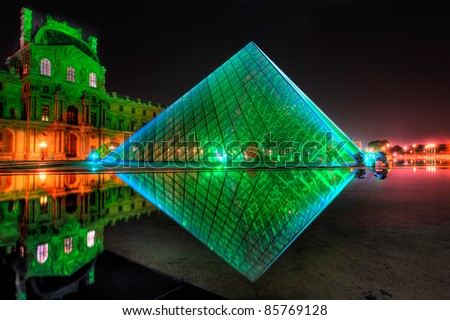 PARIS - SEPTEMBER 25: Louvre Pyramid shines at night on September 25, 2011 in Paris, France. The Louvre is the biggest Museum in Paris displaying over 60,000 square meters of exhibition space. - stock photo