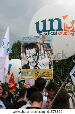 """PARIS - SEPTEMBER 23: Students carry a poster 'Sarkozy gives 15 million for the rich and for the students..."""" at the strike against raise of the retirement age on September 23, 2010 in Paris, France - stock photo"""
