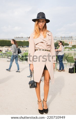 PARIS - SEPTEMBER 30, 2014: Stylish european woman with black hat and Chanel dress in the Tuileries Garden. Paris Fashion Week: Ready to Wear 2014/2015 is held from September 23 to October 1, 2014. - stock photo