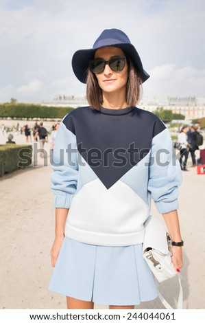 PARIS - SEPTEMBER 30, 2014: Stylish european woman with blue dress in the Tuileries Garden. Paris Fashion Week: Ready to Wear 2014/2015 is held from September 23 to October 1, 2014. - stock photo