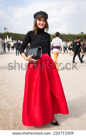 PARIS - SEPTEMBER 30, 2014: Stylish european woman with red skirt in the Tuileries Garden. Paris Fashion Week: Ready to Wear 2014/2015 is held from September 23 to October 1, 2014. - stock photo