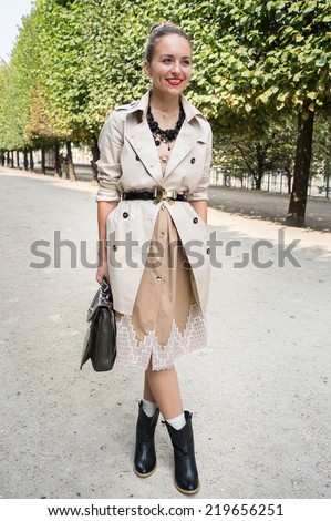 PARIS - SEPTEMBER 24, 2014: Stylish european woman with trench coat in the Tuileries Garden. Paris Fashion Week: Ready to Wear 2014/2015 is held from September 23 to October 1, 2014. - stock photo