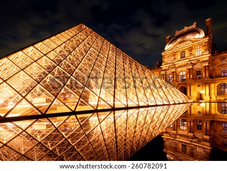 PARIS - SEPTEMBER 25, 2013: The famous glass pyramid at the Louvre. The Louvre is one of the largest museums in the world and one of the major tourist attractions of Paris. - stock photo