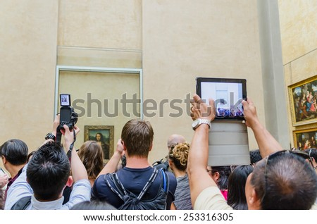"PARIS - SEPTEMBER, 17: Visitors taking photos of Leonardo DaVinci's ""Mona Lisa"" at the Louvre Museum on September, 2014 in Paris, France. Gioconda is one of the world's most famous pictures. - stock photo"