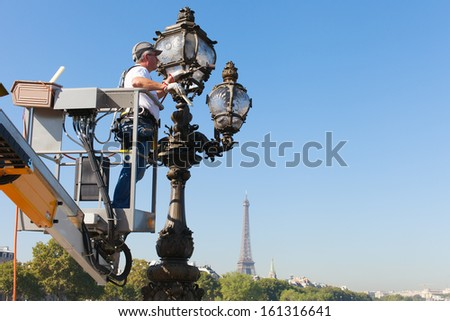 PARIS - SEPTEMBER 4: Worker cleaning street lamp on Pont Alexandre III (Alexandre III bridge) on  september 4, 2013 in Paris, France.