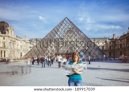 PARIS - 24 SEPTEMBER 2011 : Young female tourist observes a map of Paris in front of the Louvre Museum on September 24, 2011 in Paris. The Louvre museum is the most visited art museum in the world. - stock photo