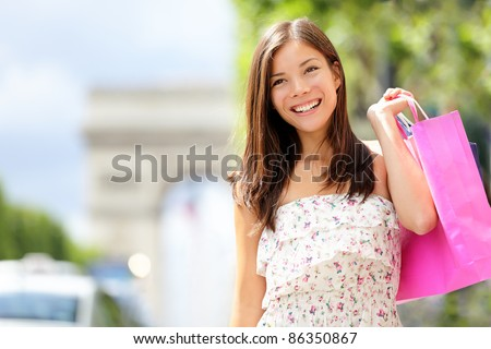 Paris shopping woman on holidays in france walking holding shopping bags in front of Arc de Triomphe while shopping on Champs-Elysees, Paris, France. - stock photo