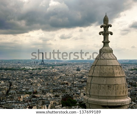 Paris sprawls out beneath the spire of the Sacre Couer, with the Eiffel Tower in the distance - stock photo