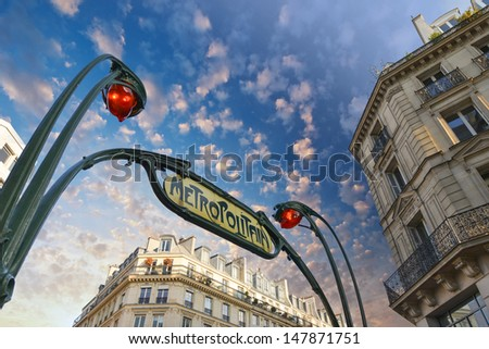 Paris. Underground Metro sign with buildings and sunset colors.
