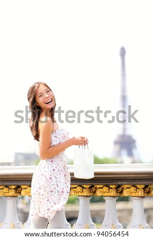 Paris woman happy and smiling - Eiffel Tower in background. Beautiful joyful young multiracial woman enjoying her Paris travel.