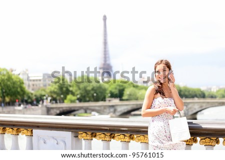 Paris woman talking on mobile phone / smart phone in Paris, France with Eiffel Tower in background. Cute beautiful multiracial Asian / Caucasian female model holding small shopping bag. - stock photo