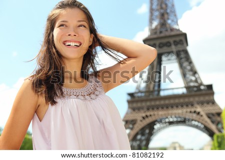 Paris woman tourist at Eiffel Tower smiling happy. Beautiful Caucasian Asian girl enjoying her Paris travel. - stock photo