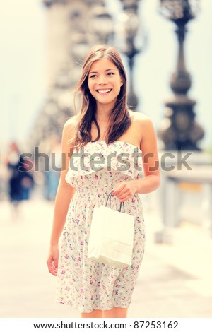 Paris woman walking with shopping bag in beautiful summer dress. Fresh natural interracial Asian Caucasian female model smiling happy in Paris, France walking on bridge over the Seine river. - stock photo