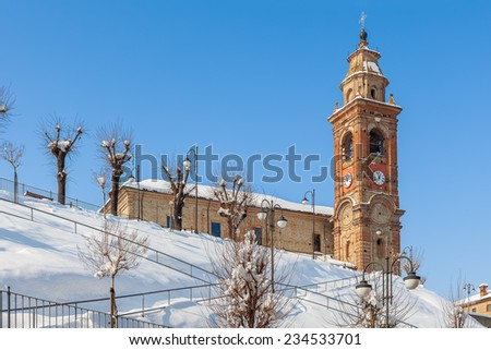 Parish church on the hill covered with snow under blue sky in small town in Piedmont, Northern Italy. - stock photo