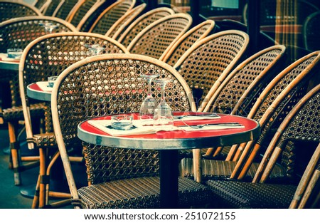 Parisian cafe terrace. Selective focus on the glasses. Aged photo. - stock photo