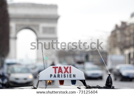 Parisian taxi on avenue des champs-elysees, with the Arc de Triomphe and traffic in the background - stock photo