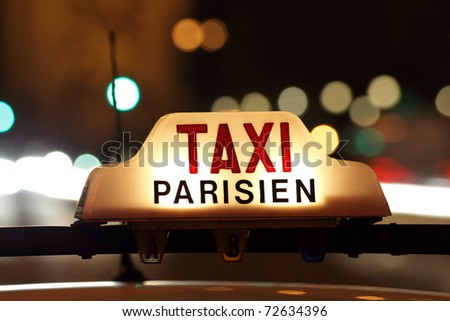Parisian taxi, with the Arc de Triomphe and traffic light trails in the background