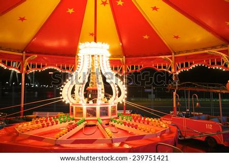 park at night; illuminated carousel  - stock photo