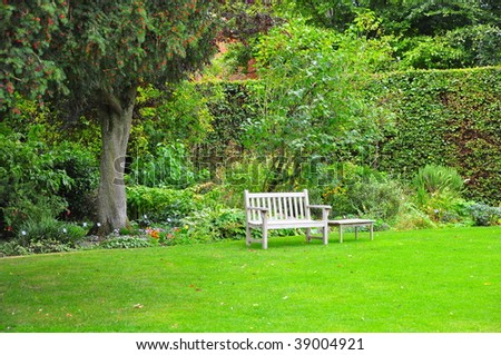 Park Bench in a cottage garden - stock photo