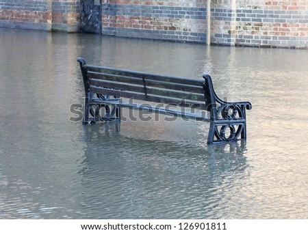 Park bench in a river flood at York, UK. - stock photo