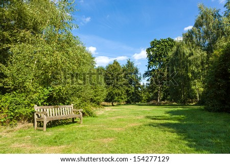 Park Bench in Beautiful Sunny and Shady Lush Green Garden - stock photo