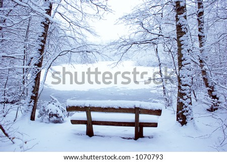 Park bench in the snow with a pool in the background - stock photo