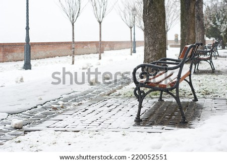 park bench on a winter alley at snowfall - stock photo