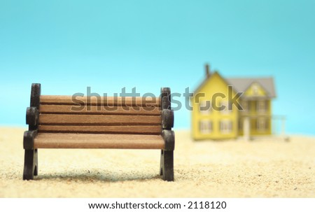 Park Bench on Sand With House in Background, Shallow DOF - stock photo
