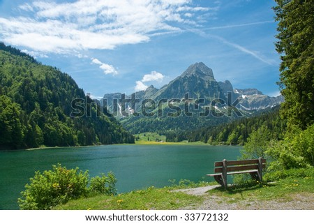 Park bench on shore of mountain lake - stock photo