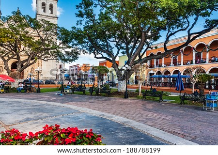 Park benches, the cathedral and colorful buildings in San Francisco de Campeche, Mexico - stock photo