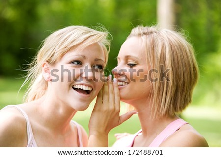 Park: Girls in Pink Whispering To Each Other - stock photo