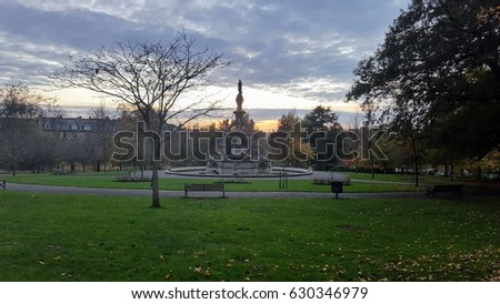 Park in Glasgow and clouded sky during sunset