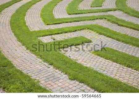 Park maze with a cobblestone walkway and grass boundaries. Horizontal shot. - stock photo
