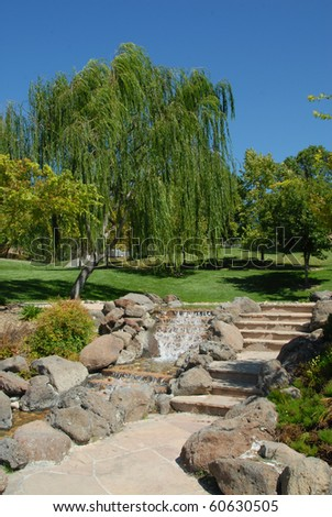 Park Pathway And Steps By Lush Creek Waterfall - stock photo
