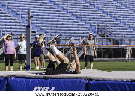 PARK RIDGE, ILLINOIS, USA - July 23, 2015: A senior high jumper lands safely  during a track and field event in the Six-County Senior Games, held by the Illinois Park and Recreation Association. - stock photo