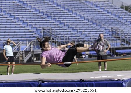 PARK RIDGE, ILLINOIS, USA - July 23, 2015: A woman high jumper tries to clear the bar during the Six-County Senior Games, held by the Illinois Park and Recreation Association, in suburban Chicago. - stock photo