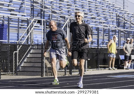 PARK RIDGE, ILLINOIS, USA - July 23, 2015: Two senior competitors sprint in a 50-meter race during senior games held by the Illinois Park and Recreation Association in suburban Chicago. - stock photo