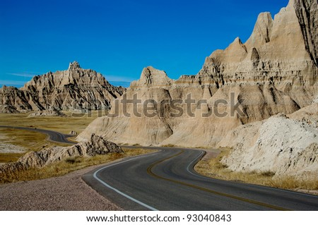 Park Road:  A paved road winds through Badlands National Park. - stock photo