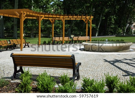 Park with fountain, benches, and wooden construction around - stock photo