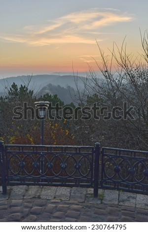 Park with lamp and paving on a sunrise with silhouettes of mountains and trees