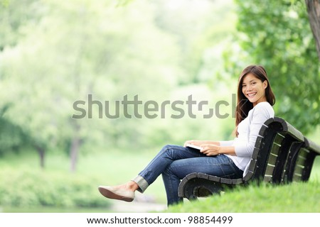 Park woman reading book on bench smiling happy at camera. Pretty young multicultural woman enjoying spring in park. - stock photo