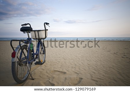 Parked bicycle along an empty beach - stock photo