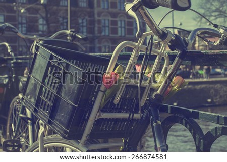 Parked bicycle on a railing in the historic canal belt, Amsterdam, The Netherlands  - stock photo