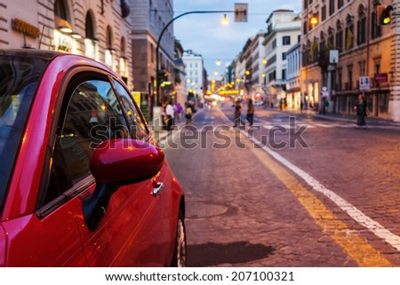 parked car with the blurred city traffic in the background at dusk - stock photo